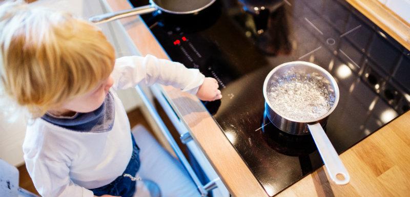 Garçon enfant en bas âge dans une situation dangereuse proche des plaques de cuisson