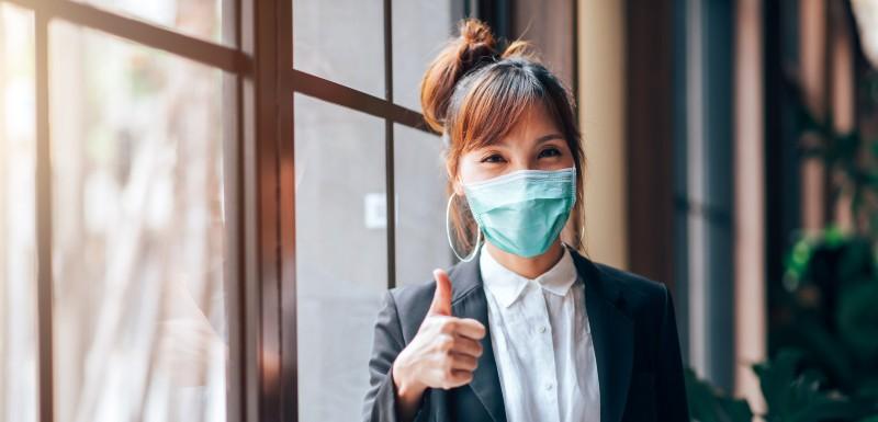 Jeune femme qui porte un masque faisant signe que tout va bien avec le pouce en l'air